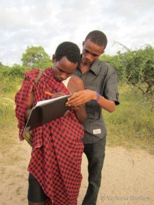 Coordinator George training LG Daudi on how to fill out the Spoor counting data form